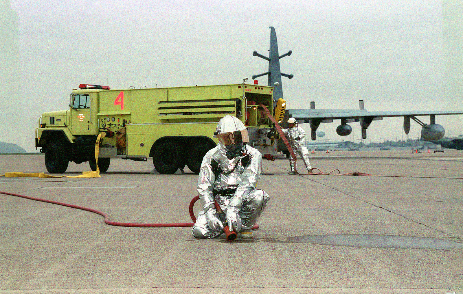 On the flight line at the 193rd SOW, a member of the 193rd Civil Engineering Fire/Crash Rescue Personnel kneals in preperation of extinguishing an aircraft fire during the Ability To Survive and Operate (ATSO) excercise