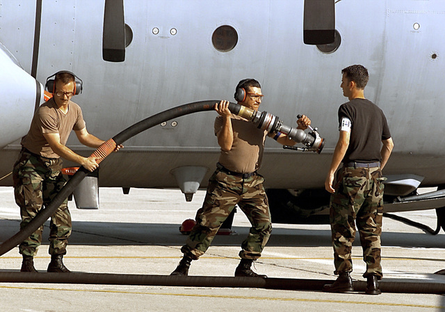 Medium shot. L to R SSGT Calvin Frost, 39th crew chief, and TSGT John Garza, 40th crew chief, prepare to refuel a C-130 during the refuel competition at Rodeo 2000. They just completed a very successful refuel and are returning the hose to a Pope POL troop