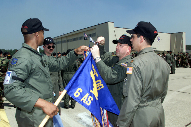 Staright on medium close-up shot from left to right as US Air Force SSGT Lew Holston, LTC Dan Weekes, and MAJ Phil Iannuzzi of the 305 Air Mobility Wing, McGuire AFB, New Jersey, prepare the 6 Airlift Squadron's flag before the Rodeo 2000 opening ceremony at Pope Air Force Base on May 7, 2000 during the Rodeo 2000 readiness competition. During the one week competition, more than 100 teams and 2,500 personnel from over 300 Air Force, Air Force Reserve, Air National Guard, U.S. Army units, and foreign nations will compete in airdrops, cargo loading, refueling, pre-flight, combat endurance, combat tactics, as well as other air and ground operations (Army units, foreign nations, airdrops, ...