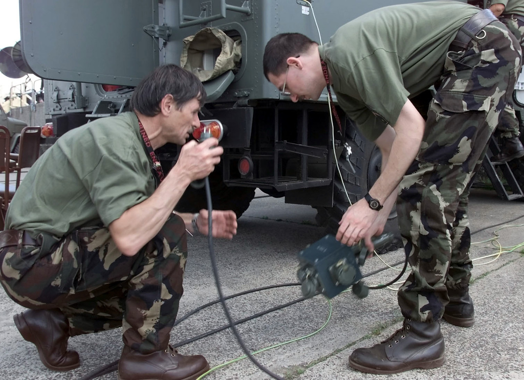 Hungarian Army Lieutenant Colonel (LTC) Ivan Bene (left) and a member of the Hungarian Team connects power to the Microwave Station and Mark 1 switch equipment during Exercise COMBINED ENDEAVOR 2000. The Exercise is a Partnership for Peace (PfP) exercise hosted by Germany and is the largest information and communications systems exercise in the world which focuses primarily on Command, Control, Communications, and Computers (C4) interoperability testing and documentation