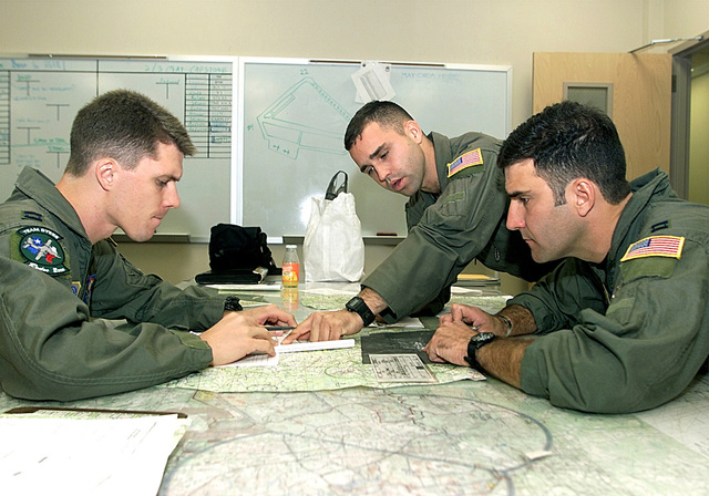 Medium close shot. Lto R Flight Crew, CPT Joseph Speight (Nav), 1Lt Dave Jesurun (co-pilot), and CPT Jerry Steen (pilot), go over the route study during mission planning for the air drop mission