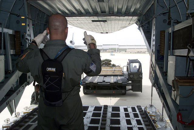 Interior straight on rear view, medium shot as US Air Force STAFF Sergeant Lew Holston of the 6 Airlift Squadron, McGuire AFB, New Jersey, prepares to load cargo before an air drop event on May 10, 2000 during the Rodeo 2000 readiness competition. During the one week competition, more than 100 teams and 2,500 personnel from over 300 Air Force, Air Force Reserve, Air National Guard, U.S. Army units, and foreign nations will compete in airdrops, cargo loading, refueling, pre-flight, combat endurance, combat tactics, as well as other air and ground operations (Air Force Reserve, Air National Guard, US Army units, foreign nations, air drops, refueling, pre-flight, combat endurance, combat ...