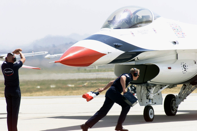 An USAF Thunderbird Aerial Demonstration Team F-16 Fighting Falcon aircraft is marshaled to a stop by crewmembers on the flight line at March Air Reserve Base (ARB), California (CA) during the Airfest 2000 air show