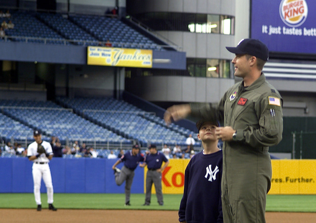Left side profile medium close-up shot as US Air Force Special Operations helicopter pilot, Captain Bill Denehen throws the ceremonial first pitch at Yankee Stadium on 11 may 2000. On May 2, 1999, while assigned with the 55th Special Operations Squadron, CPT Denehen and his crew courageously penetrated one of the most sophisticated air defense networks in the world to rescue an F-16C pilot (not shown) trapped deep inside of Serbia. This was the first mission in history where a special operations rescue force penetrated and successfully defeated an active integrated air defense system of a determined military. During Operation Allied Force