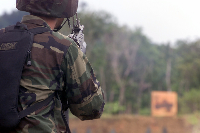 Private First Class (PFC) Jesus Hanna, USA, 1ST Battalion, 501st Infantry, takes aim on the target down range with his 5.56mm M16A1 assault rifle, with an 40mm M203 grenade launcher attached, during combined live fire exercises held at Thung Song, Thailand, during Exercise COBRA GOLD 2000