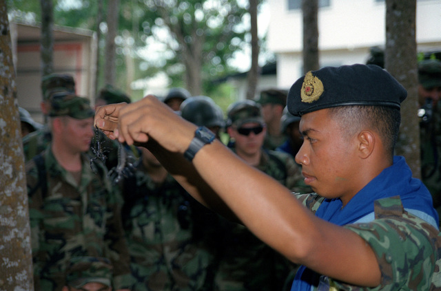 Royal Thai Army First Lieutenant (1LT) Pansak Thongsuk, Platoon Leader, 2nd Battalion, 15th Infantry Regiment shows Army soldiers assigned C/Company, 1ST Battalion, 501st Parachute Infantry Regiment, two types of deadly scorpions, during Jungle Survival Training at Thong Song, Thailand during Exercise COBRA GOLD 2000