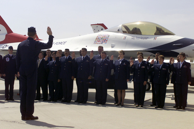 US Air Force (USAF) Major (MAJ) John Venable, a member of the USAF Thunderbirds Aerial Demonstration Team, issues the oath of reenlistment to members of the US Air Force Reserve (USAFR) in front a USAF Thunderbirds F-16 Fighting Falcon aircraft on the flight line at March Air Reserve Base (ARB), California (CA) during the Airfest 2000 air show