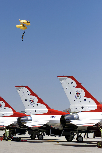 "Members of the US Armyßs""Golden Nights"", Parachute Team float towards the earth during the Airfest 2000 air show held at March Air Reserve Base (ARB), California (CA). Several USAF Thunderbirds F-16 Fighting Falcon aircraft are parked in the foreground"
