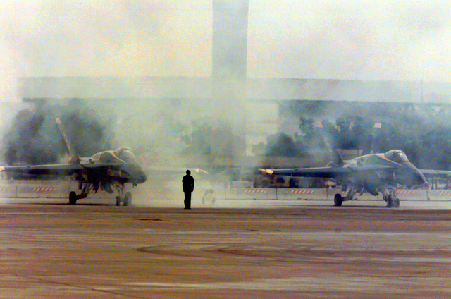 Two U.S. Navy Blue Angels, F-18 Hornet aircraft run-up their engines on takeoff during the Joint Services Open House 2000