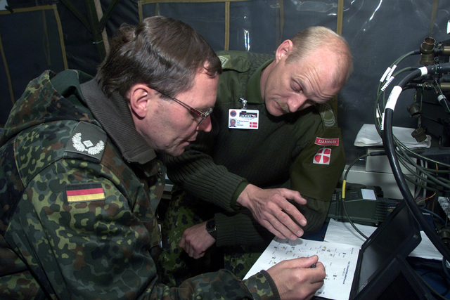 Army Warran Officer (WO) Ib Burge Nielson, (rear), Local-Area Nework/Wide Area Nework (LAN/WAN) Technician, Denmark, and Army Major (MAJ) Edmar Knies, LAN/WAN Technician, Germany, discuss he proper connecions beween daa and phones o be used for Phase 3 esing during COMBINED ENDEAVOR (CE) 2000 held a Lager Aulenbach, Germany. CE 2000, currenly hosed by Germany, is he larges informaion and communicaion sysems exercise in he world. This exercise is he sixh in a series of mulinaional communicaion ineroperabiliy workshops where miliary personnel from 35 naions ge ogeher for 14 days o focus on Command, Conrol, Communicaions, and Compuers (C4) ineroperabiliy...