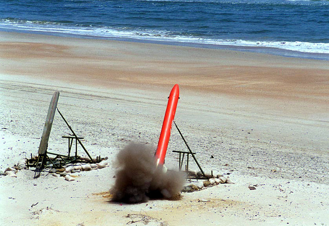 """A United States Army remote-controlled """"B.A.T.S."""" target rocket, at the moment of lift-off from its launchpad, on the E-1 range at Camp Lejeune's Onslow Beach area during a 2nd Low Altitude Air Defense (LAAD) Battalion missile targeting exercise. Marines from the 2nd LAAD Battalion, stationed at Marine Corps Air Station Cherry Point, North Carolina, were using the versatile rockets as fast-moving targets, firing Stinger missiles at them from the Avenger system mounted atop High-Mobility Multipurpose Wheeled Vehicles (HMMWV) (not shown)"""