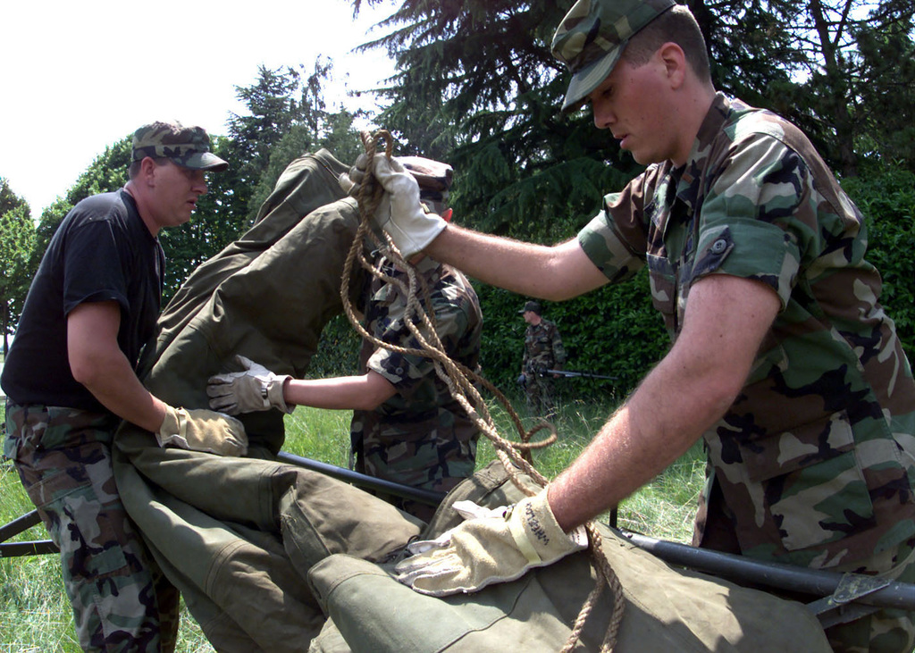 Closest to the camera, US Air Force 2nd Lieutenant David J. Wheelock, a Communications Information Systems Officer and SENIOR AIRMAN Brian Coleman, A Satellite Communications Journeyman download tents during Exercise RESCUE VENETO