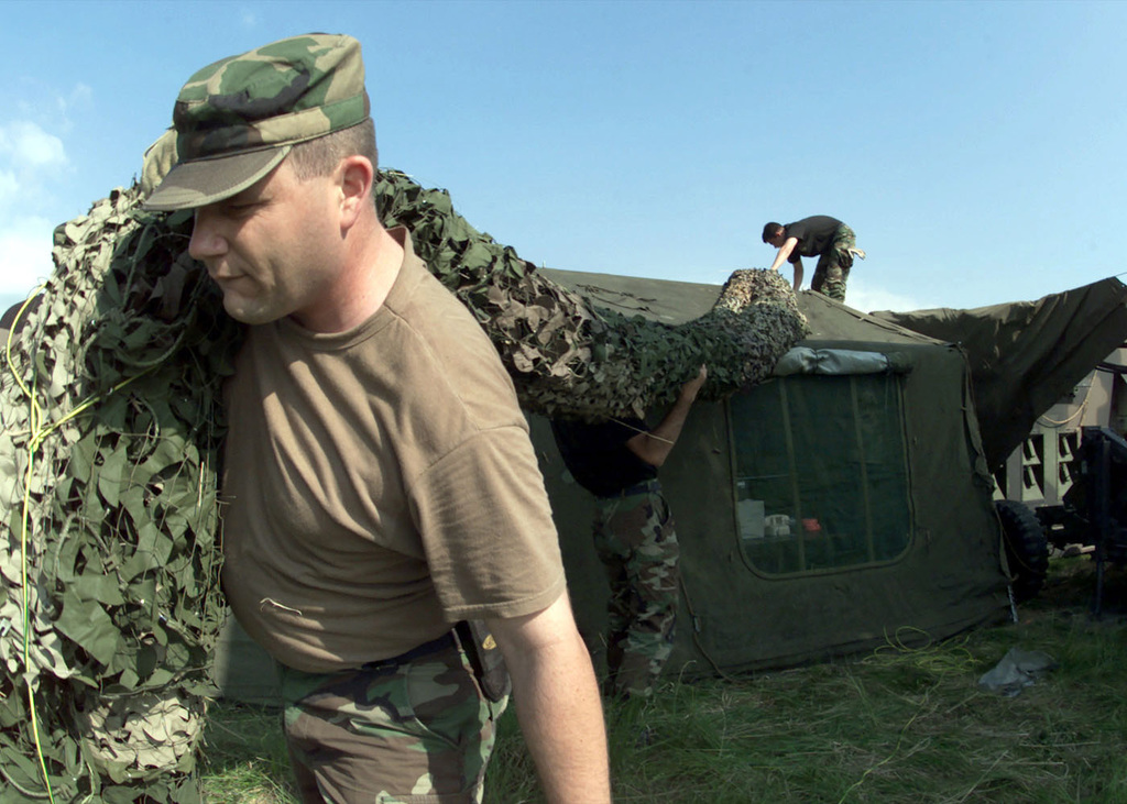 US Air Force MASTER Sergeant Russell E. Wright (Foreground), a Radar Maintenance Craftsman of the 31st Communications Squadron, Aviano Air Base, Italy, pulls the camouflage netting used to hide the radar site, over the communications tent on the first day of set-up during Exercise RESCUE VENETO