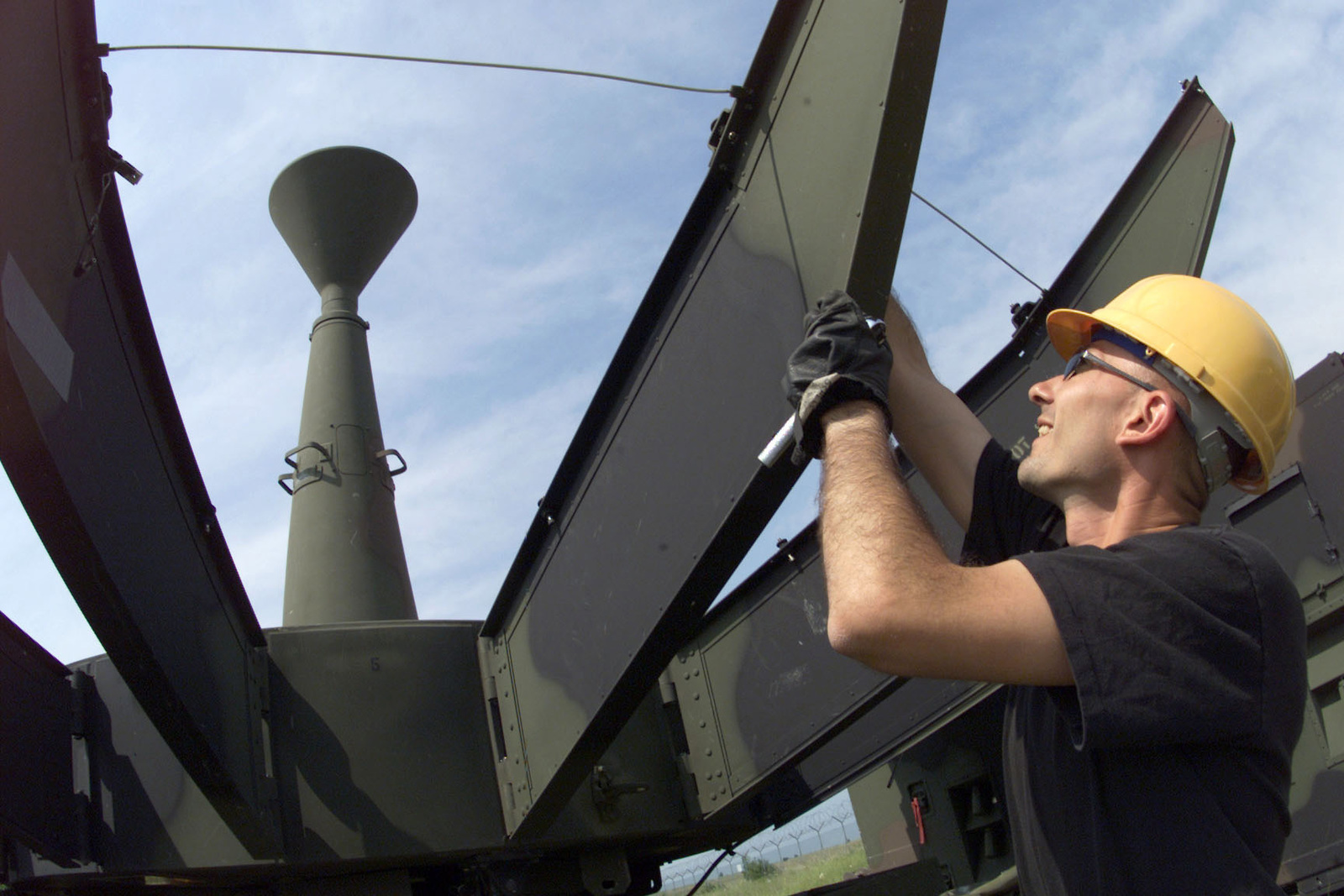US Air Force STAFF Sergeant Thomas A. Schell, a Satellite Wideband Communications Journeyman for the 31st Communications Squadron, Aviano Air Base, Italy, rotates and locks the petal supports of a communications dish into place, during VENETO RESCUE on May 31st, 2000