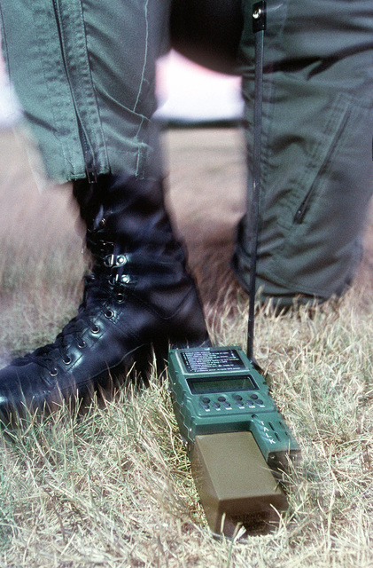 "A medium close up view of the AN/ PRC-112B (HOOK-112), Search and Rescue Transceiver. The hook-112 is placed on the ground next to someones foot for size comparison. From the June 2000 AIRMAN Magazine article ""Taking 'Search' out of Search and Rescue."""