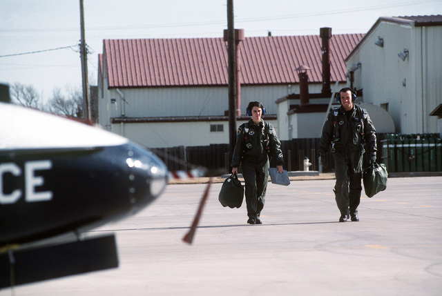 "US Air Force Captain Mike Brazelton an instructor pilot at training at Vance AFB, Oklahoma and 2nd Lieutenant Molly Morris walk toward a T-37 Tweet aircraft to begin her evaluation flight. From then June 2000 AIRMAN Magazine article ""Silver Wing Strut"" describing Joint-service pilot training at Vance AFB, Oklahoma"