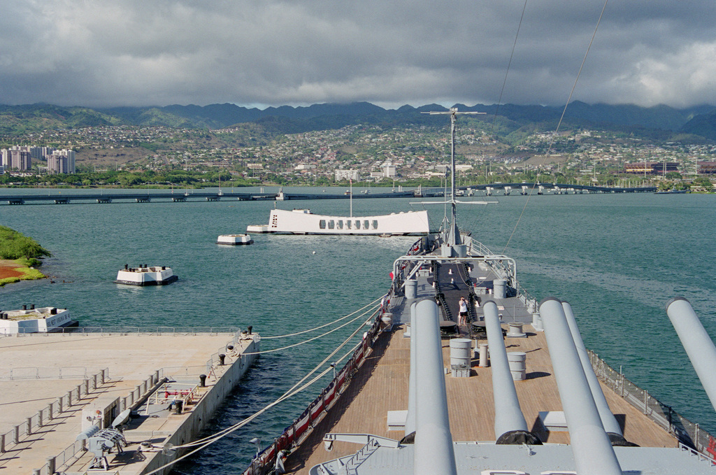 View from the bridge of the memorial battleship USS MISSOURI (BB-63) looking up battleship row toward the USS ARIZONA (BB 39) which spans the sunken battleship lost on December 7, 1941. In the background is the Admiral Bernard Clarey Bridge to Ford Island. Aiea Heights is in the distant background