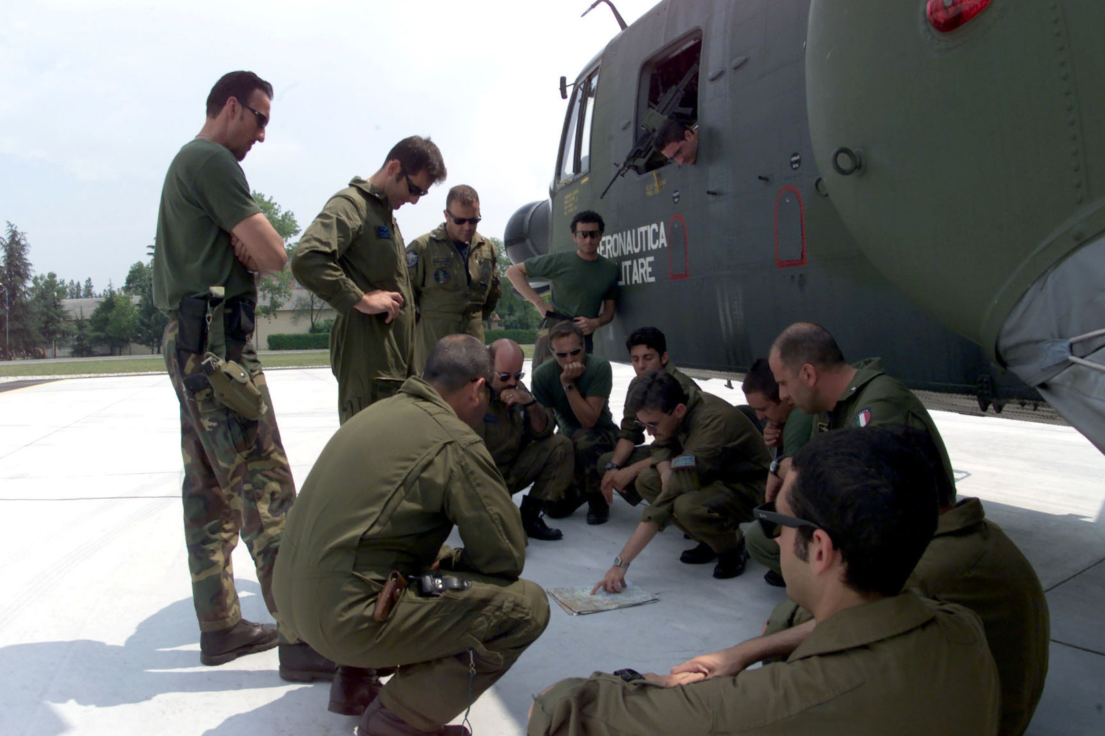 Italian Air Force Lieutenant Nanni Adrea (Pointing at map), briefs the two crews of the Italian CSAR( Combat Search And Rescue) crews that are simulating extraction of NEO (Non-combatant Evacuation Operation) evacuees during Exercise VENETO RESCUE on June 6th, 2000