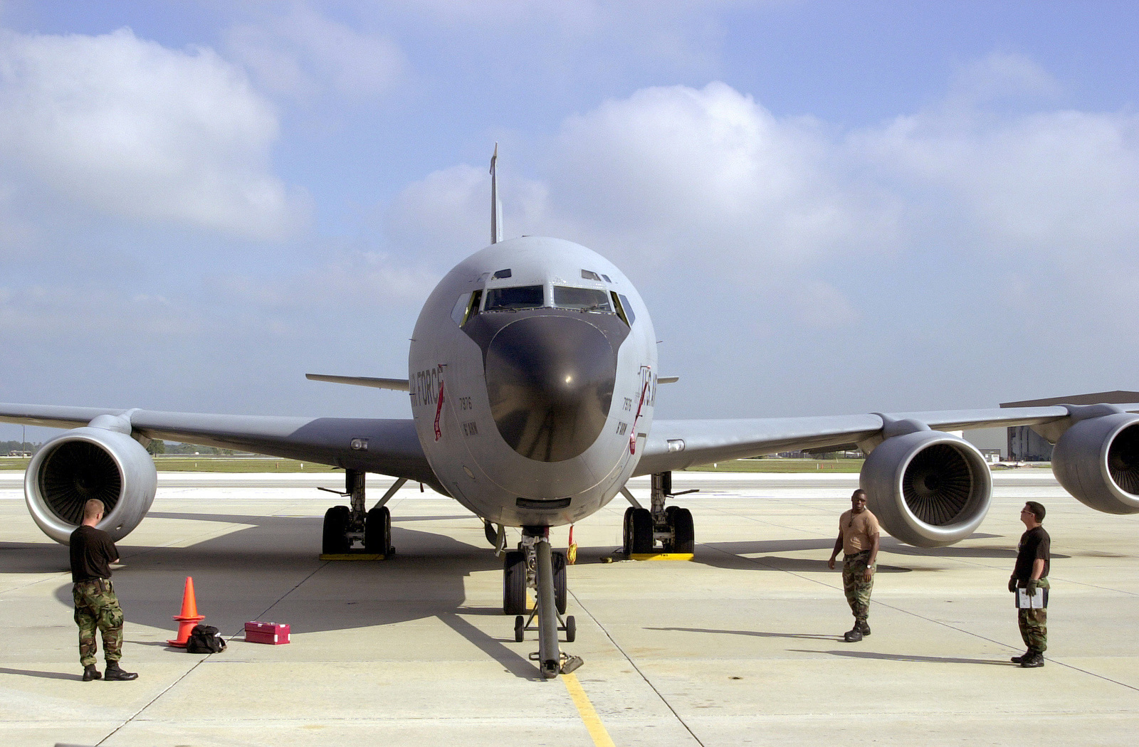 Straight on medium shot of a US Air Force KC-135 Stratotanker from MacDill Air Force Base, Florida. Standing in front of the aircraft are (From left to right), SENIOR AIRMAN Nick Demarco, Flying Crew CHIEF, SRA Nate Roberson, Hydraulic SPECIALIST and STAFF Sergeant Nick Bardash, Flying Crew CHIEF. All three are from the 6th Aircraft Generation Squadron and are preparing the KC-135 for towing to MacDill's fuel pit (Not shown)
