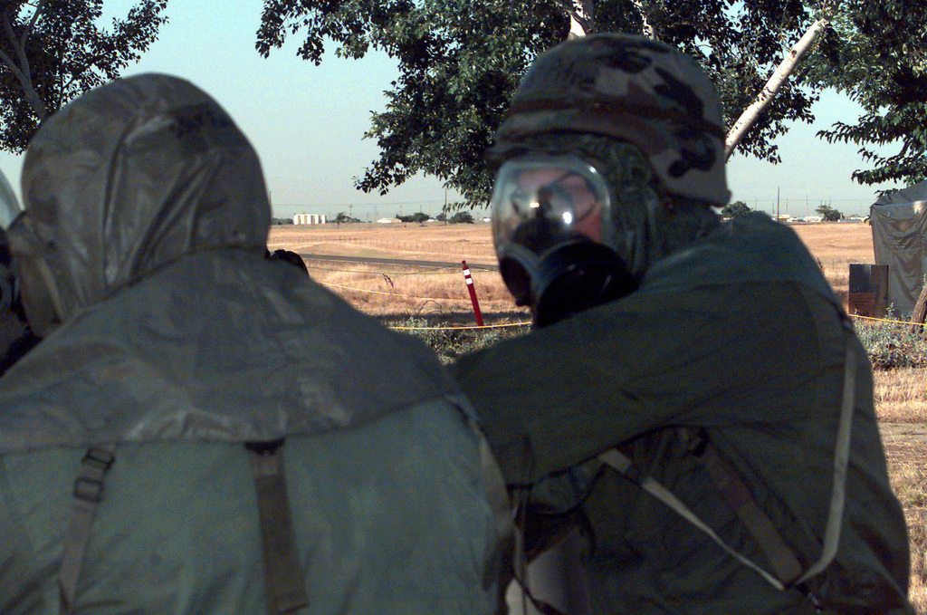 US Air Force Sweep team members, in Mission-Oriented Protection Posture response level 4 (MOPP-4) gear, are surveying the base for Unexploded Ordnance (UXO) during a Combat Readiness Exercise (CRE) 00-02 at Beale Air Force Base, California