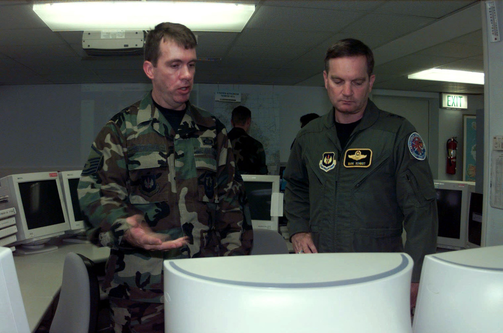 US Air Force MASTER Sergeant Michael Butroeich (Left), the Assistant Flight CHIEF, USAFE Operational Weather Squadron, Sembach Air Base, Germany, briefs USAF Major General Mark Schmidt. MGEN Schmidt, newly arrived to Europe, is the United States Air Force Europe Director of Aerospace Operations, Ramstein AB, DEU. He was given a brief tour of the USAFE Operational Weather Squadron facility and an opportunity to shake hands with each individual personnel