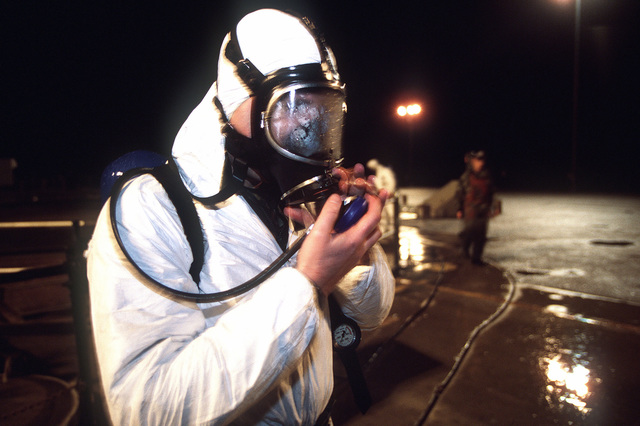 "A US Air Force maintainer protects himself from sulfuric hydrochloric acids by wearing protective clothing and a breathing apparatus before removing vital launch parts from a Peacekeeper missile silo located at Vandenberg AFB, CA. From AIRMAN Magazine, July 2000 article ""Peacekeeper 2000."""