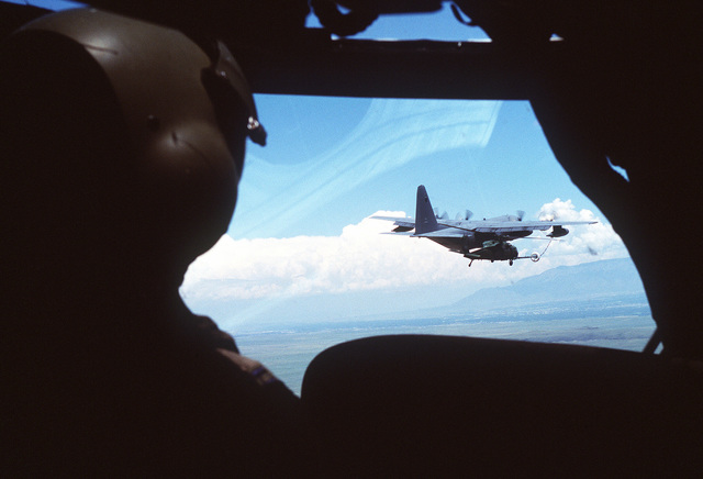 """An aerial view of a US Air Force MC-130P Combat Shadow aircraft refueling a MH-60G Pave Hawk helicopter. The photo was taken from inside the cockpit and over the pilots shoulder of an unidentified aircraft. From AIRMAN Magazine, July 2000 article """"Front Cover."""""""