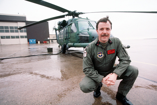 """Royal Air Force Squadron Leader Trev Rutherford, a British Exchange office kneels for a photo in front of a US Air Force HH-60G helicopter at Kirtland AFB, New Mexico. From AIRMAN Magazine, July 2000 article """"Front Cover."""""""