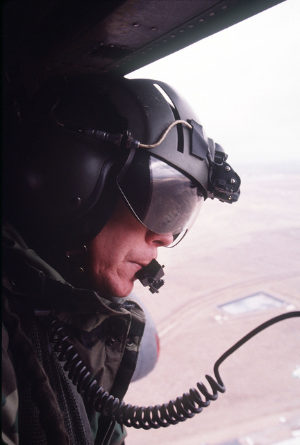 """US Air Force Technical Sergeant Phil Fraley an instructor at the 58th Special Operations Wing at Kirtland Air Force Base, New Mexico, scans out the open window of the right gunner's door for aircraft and obstacles during a recent training flight aboard a MH-53J Pave Low III E helicopter. From AIRMAN Magazine, July 2000 article""""Front Cover"""""""