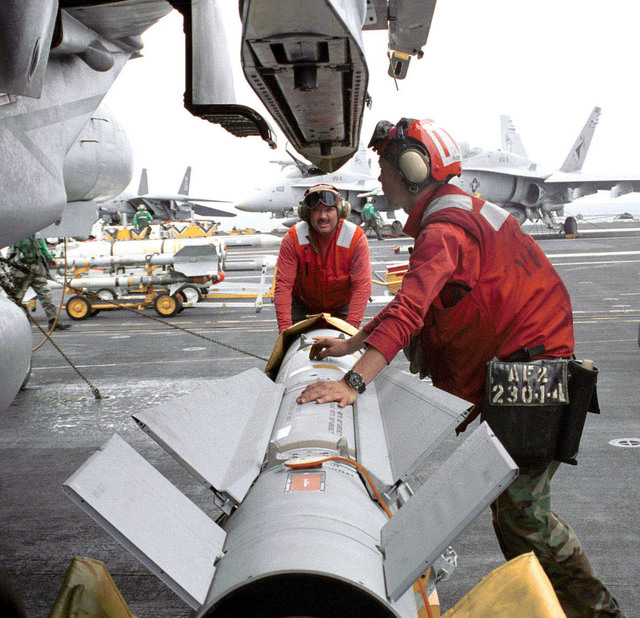 "Aboard the USS GEORGE WASHINGTON (CVN 73), Aviation Ordnanceman 1ST Class (AO1) Andrew T. Martinez from Alamos, Colorado and Aviation Ordnanceman AIRMAN (AOAN) Jason L. Harsem of Pequanoch, New Jersey, load an AIM-54C ""Phoenix"" missile up under an F-14B ""Tomcat"" wing. The aircraft is assigned to the ""Jolly Rogers"" of Fighter Squadron One Zero Three (VF-103)"