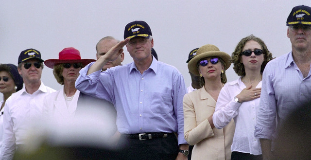 President William Clinton, accompanied by his family, Secretary of the Navy Richard Danzig (right) and Secretary of Defense William Cohen pay their respects to the national ensign, during the Pledge of Alliegence aboard the USS JOHN F. KENNEDY (CV 67), on July 4, 2000, during the International Naval Review 2000 held in New York City, New York