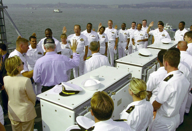 President William Clinton, accompanied by the First Lady, Hillary Rodham-Clinton, reads the oath of a reenlistment to a group of sailors aboard USS HUE CITY (CG 66), on July 4, 2000