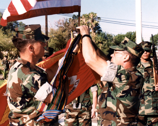 US Marine First Sergeant Charles J. Allen III, Headquarters Battalion First Sergeant (left) and Colonel Mark A. Costa, Base Commander of Marine Corps Logistics Base, Barstow (MCLB), California, pin the Meritorious Unit Commendation (MUC) streamer to the organizational colors. It is MCLB's 4th award of the MUC