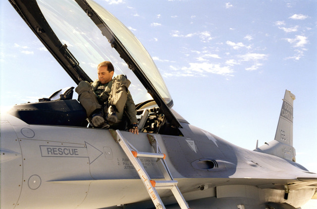 Climbing into the cockpit on the ramp at Hill Air Force Base, Utah. Lieutenant Colonel Dean Pennington, 157th Fighter Squadron Commander, McEntire Air National Guard Station, South Carolina, prepares for his first flight of the exercise. The 169th Fighter Wing of the South Carolina Air National Guard, McEntire Air National Guard Station, is deployed to Hill Air Force Base, Utah to participate in Combat Hammer. It's flying squadron, the 157th Fighter Squadron (FS), is one of several units operating in this 'live-fire' weapons testing mission. The 157th FS will fire Highspeed Anti-Radiation Missiles (HARM) and AGM-65G Maverick missiles to test their pilots abilities, their unit tactics, and...