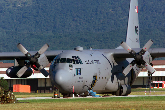 Left side front view medium long shot as a Ramstien Air Base C-130E stands ready at Aviano Air Base Italy to deliver an Army airborne unit (Not shown) into Bosnia for Rapid Resolve II, a show of force exercise, 17 july 00