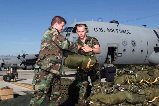 Right side profile medium shot as US Army Sergeant Frederik Webb (left) and SPECIALIST Arron Lincoln (right) Eco company 1ST 508 out of Vicenza Italy prepare parachutes at Aviano Air Base Italy for Operation Rapid Resolve II, a show of force air drop in Bosnia, 17Jul00. A left side front view medium shot of a US Air Force C-130 Hercules is seen in the background