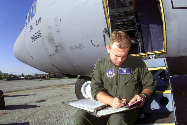 Straight on medium close-up shot as US Air Force Technical Sergeant Max Rentfrow from the 37th Airlift Squadron Ramstien Air Base Germany plans the take off and landings for Operation Rapid Resolve II, a show of force exersise in Bosnia, 17 July 00