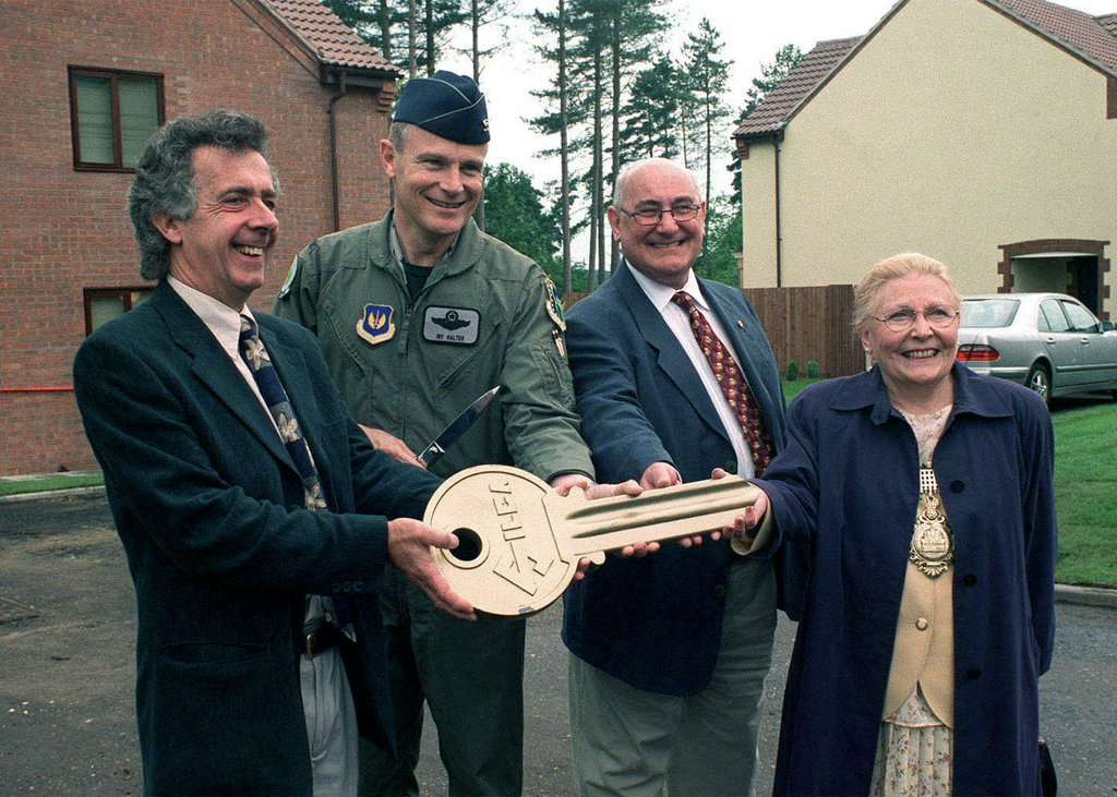 Straight on medium shot as from left to right, Jeff Collett, Area Director for Carillion Construction, US Air Force Colonel (COL) Irv Halter, 48th Fighter Wing Commander Royal Air Force Lakenheath, United Kingdom, Boris Hayklan, Chairman of the Municipal Housing Corporation, and Jean Hay, Mayor of Thetford hand over a key to COL Halter at the 13 July 2000 grand opening of the first house. Five hundred and seventeen more houses are currently under construction in support of the leased-build initiative. The houses will be occupied by military members stationed at Royal Air Force Bases Lakenheath, Mildenhall, and Feltwell. The new housing units are located at the Lynn Wood Estate, Thetford, ...