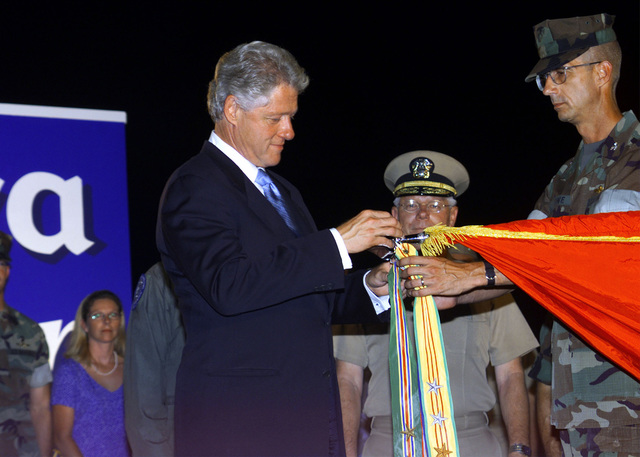 President William Jefferson Clinton and US Marine Corps Colonel James M. Lowe, Commanding Officer, 31st Marine Expeditionary Unit (MEU), attach the Meritorious Unit Citation battle streamer to the official colors of the 31st MEU during a ceremony in Okinawa, Japan. The president is visiting Japan as part of a multinational summit involving the eight leading industrialized nations