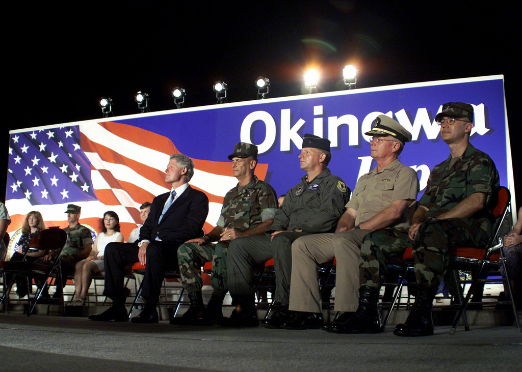President William Jefferson Clinton, US Marine Corps Lieutenant General Earl B. Hailston, US Air Force General James Smith, US Navy Admiral Paul Scholtz and US Army Colonel Micheal J. sullivan listen to STAFF Sergeant Shane Wehunt (not shown) introduce the President during the ceremony in Okinawa, Japan. The President is visiting Okinawa Japan as part of a multinational summit involving the eight leading industrialized nations