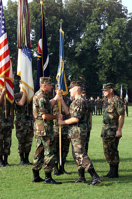 US Army Major General Geoffrey D. Miller, Deputy CHIEF of STAFF, installation and personnel management, forces command, passes the Fort McPherson garrison flag to incoming commander US Army Colonel Harold E. Cooney, as outgoing commander, US Army Colonel William D. Clingempeel, looks on