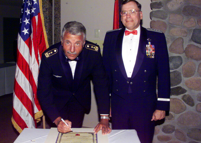 US Air Force General John Jumper (Right), COmmander, Air Combat Command, Langley Air Force Base, Virginia, and German Lieutenant General Peter Vogler, Commander, German Air Force Command, sign the Decree of Honor, cementing the relationship between the 63rd Fighter Squadron, Luke Air Force Base, Arizona, and the Luftwaffe's Cactus Starfighter Squadron during Class 00-IBG graduation