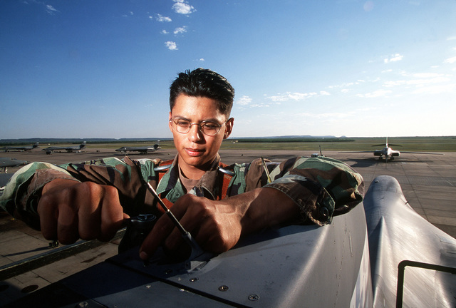 """US Air Force AIRMAN First Class Edward Vela, defensive avionics specialist, works on the avionics system high atop a USAF B-1B Lancer aircraft from the 28th Bomb Squadron, Dyess AFB, Texas parked on the flight line. From AIRMAN Magazine, August 2000 article """"One Hot Bomber."""""""