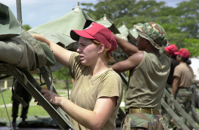 US Air Force SENIOR AIRMAN Julia Dodge, 820th RED HORSE, Nellis Air Force Base, Nevada helps bring down tents prior to departure from Grenada on August 2nd, 2000. The Air Force's 820th RED HORSE Squadron, Nellis AFB, NV, and the Marine's 8th Engineer Support Battalion, Camp Lejeune, North Carolina (Not shown), are part of a larger humanitarian exercise sponsored by USSOUTHCOM (United States Southern Command) and is tasked with constructing a community center, barracks, and a school. This exercise, New Horizons 2000, is held in various Caribbean and South American locations