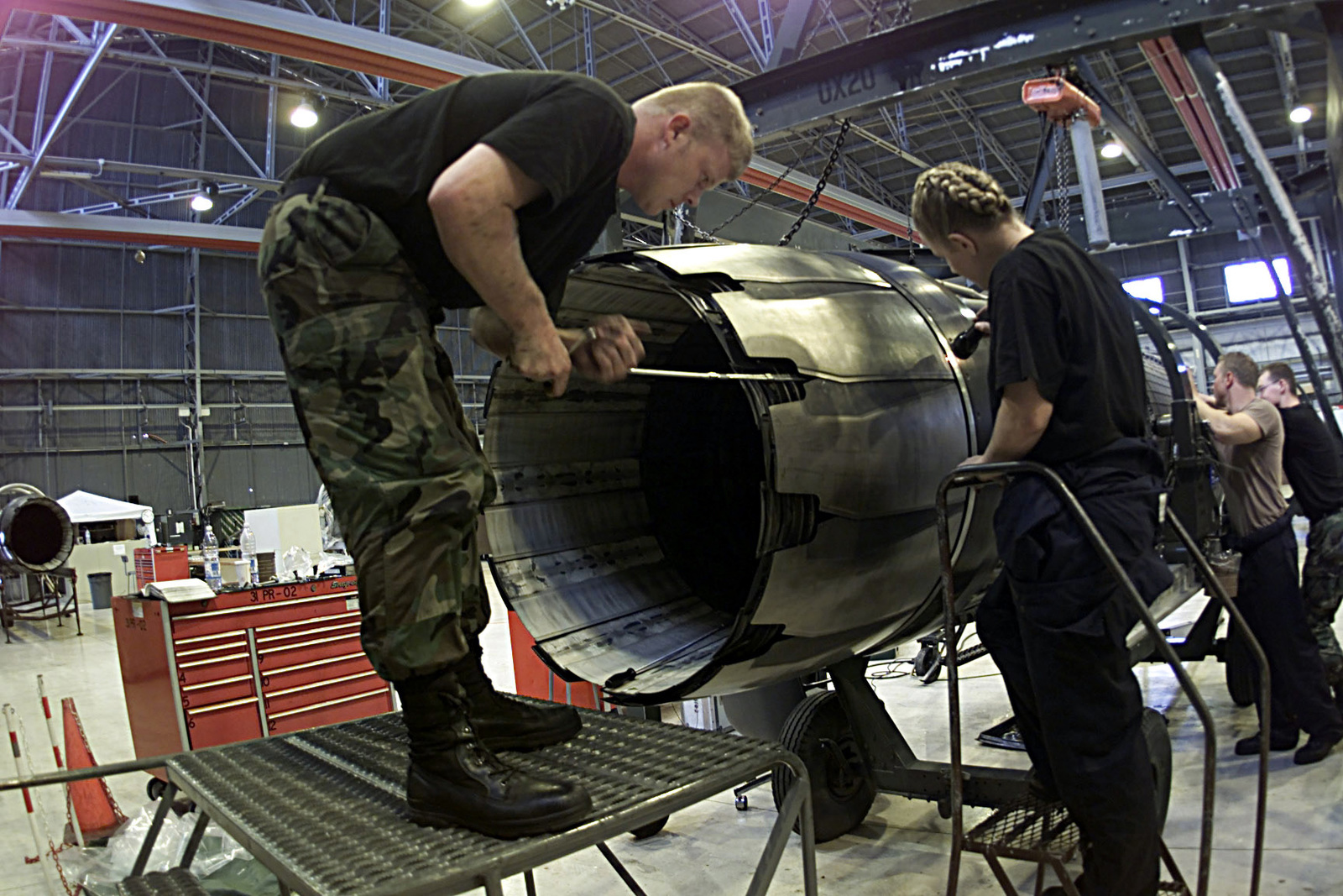 US Air Force AIRMAN First Class Curtiss Gladden (Left) and STAFF Sergeant Angel Bradshaw of the 31st Maintenance Squadron, 31 Fighter Wing, Aviano Air Base, Italy, replace the outer-flap on a F110-GE-100 engine at Aviano Air Base, ITA, on August 3rd, 2000