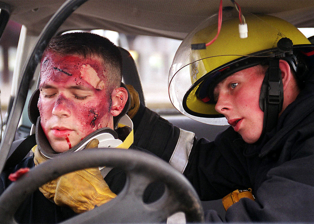 US Air Force SENIOR AIRMAN Joey LeBlanc from the 48th Civil Engineering Squadron (CES), 48th Fighter Wing, Royal Air Force Lakenheath, United Kingdom, receives a C-Collar from a member of the Suffolk Fire Brigade during a recent exercise. A C-Collar is used for neck stabilization. The 48th CES held the joint exercise with the English fire department on quick responses to aircraft and vehicle accidents. The exercise is conducted twice a year