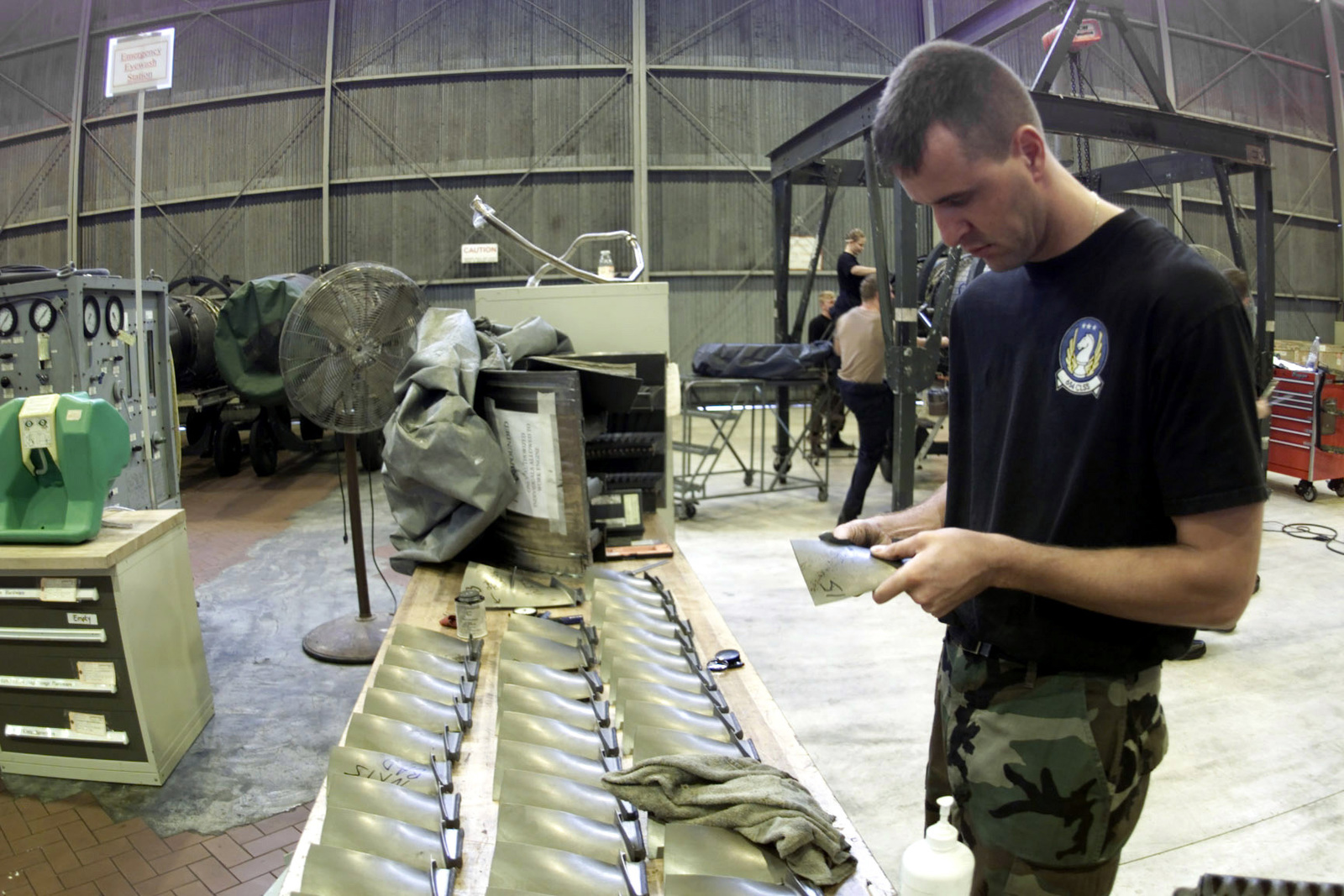 US Air Force STAFF Sergeant Shon Wagner, a Jet Engine Mechanic Craftsman of the 654th Combat Logistics Support Squadron, Tinker Air Force Base, Oklahoma, inspects the blades recently removed from an F110-GE-100 engine at Aviano Air Base, Italy, on August 3rd, 2000