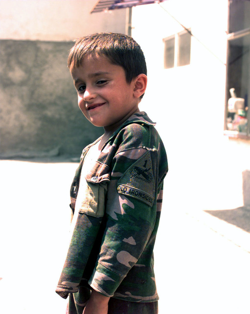 An Albanian boy bears the 1ST Armored Division (1ST AD), patch on his shoulder to show his support for US troops from the Peacekeeping forces of Kosovo Peacekeeping Force (KFOR), in Gnjilane, Kosovo