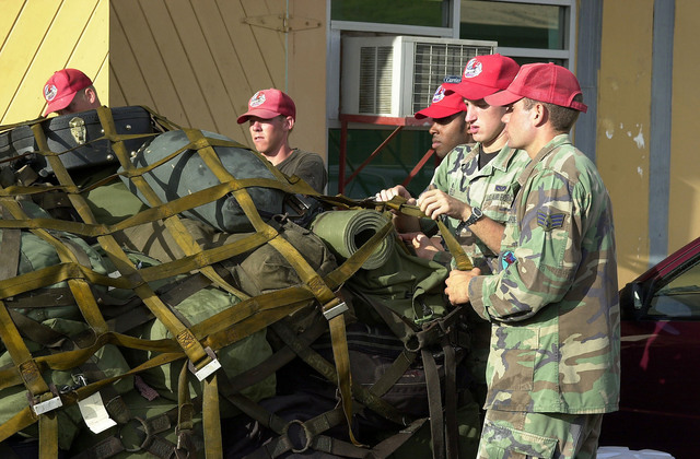 US Air Force members, 820th RED HORSE, Nellis Air Force Base, Nevada, tighten down cargo netting covering their pallet of luggage prior to departure from Grenada on August 7th, 2000. The Air Force's 820th RED HORSE and the Marine's 8th Engineer Support Battalion, Camp Lejeune, North Carolina (Marines not shown), are part of a larger humanitarian exercise sponsored by USSOUTHCOM (United States Southern Command) and is tasked with constructing a community center, barracks, and a school. This exercise, New Horizons 2000, is held in various Caribbean and South American locations