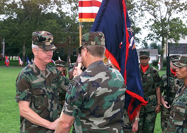Lieutenant Colonel Douglas Satterfield, left, assumes command of the 8th Battalion from 4th Brigade Executive Officer Brian Carpenter as Lieutenant Colonel Marcia Martin, right, looks on